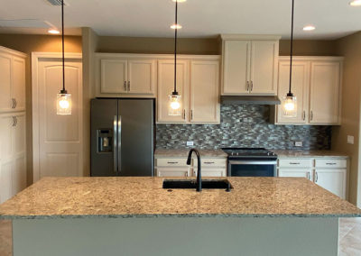 Inside a DM Dean Custom Build Home: Kitchen with island kitchen sink and silver/bronze accented tile walls